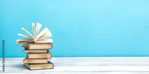 Open book, hardback books on wooden table Canvas Print