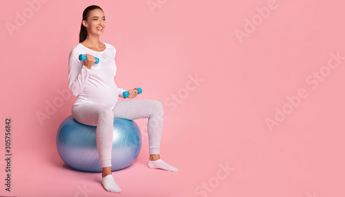 Fotografija Pregnant Girl Exercising With Dumbbells Sitting On Fitball, Pink Background