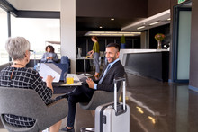 Diverse Business Partners Sitting In Modern Airport Lounge With