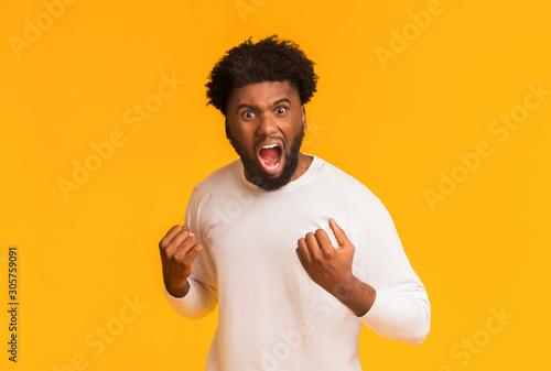 Cuadros en Lienzo Furious afro guy shouting over orange background