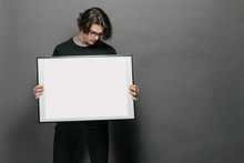 Man Holding A Picture Frame Or Poster For Mock Up Wearing Black Clothes