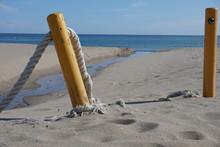 Paisaje De Mar Con El Mar, La Playa Y Un Riachuelo En El Fondo.  En Primer Plano Hay Unas Vallas De Cuerda.
