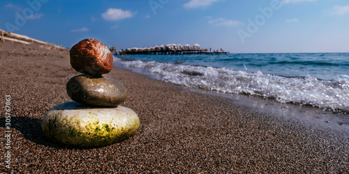 Photo sur Toile Zen pierres a sable Stack of zen stones on beach near sea. Tower of spa rocks on sand at ocean. Balanced pebbles outdoors on sunny summer day. Oriental calm and harmony symbol. Wellness and tranquility concept