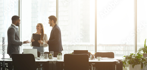 Successful businesspeople talking together in front of office windows