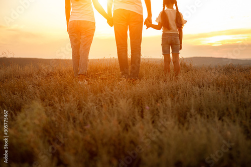 Unrecognizable family enjoying sunset in nature