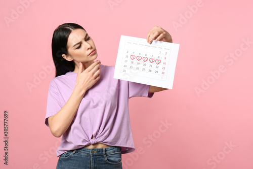 Obraz Pensive young woman holding calendar with marked menstrual cycle days on pink background - fototapety do salonu