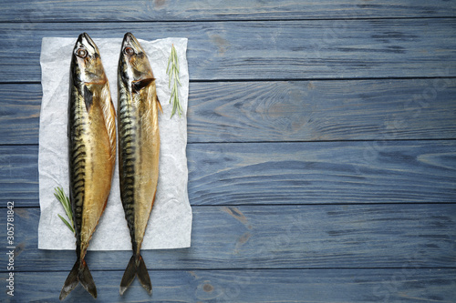 Fotografía  Tasty smoked fish on blue wooden table, top view. Space for text