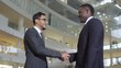 Medium shot of Asian businessman in glasses smiling while talking to black male colleague and shaking hands with him