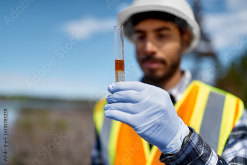 Marine biologist analysing water test results with floating oili Canvas Print