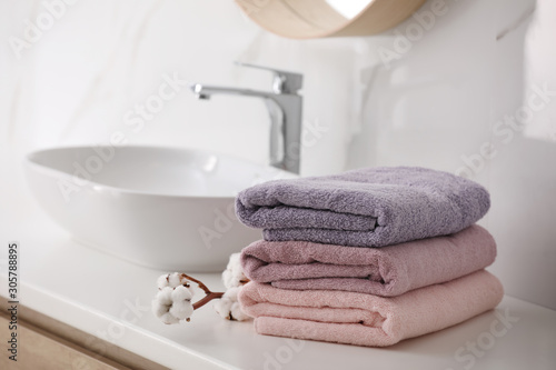 Fotografering Stack of fresh towels and cotton flowers on countertop in bathroom