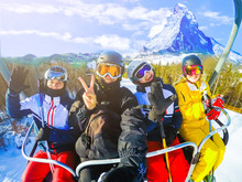 Happy Young Friends Skiers On Ski Lift Ride Up Amazing Beautiful View Ski Resort In Switzerland With Cable Chairlift Transport