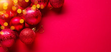 Red New Year Or Christmas Background And Sparkling Christmas Balls On It.