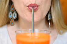 A Young Beautiful Woman Drinks An Orange Carrot Freshly Squeezed Juice With A Reusable Metal Drinking Straw