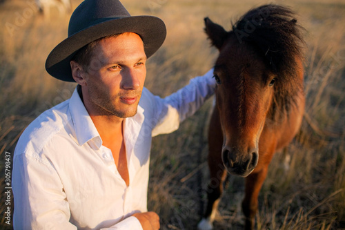 Fototapeta portrait of handsome young man and his brown horse.
