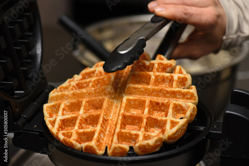 Fotomural Whole wheat waffle picked out of waffle iron with tongs