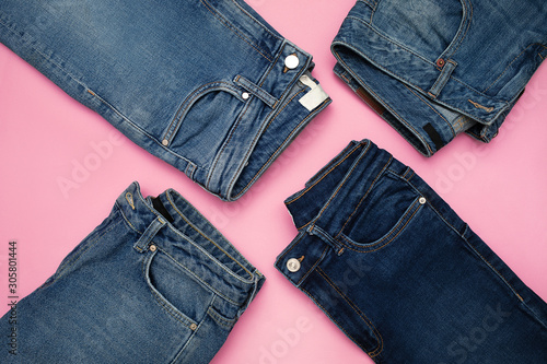 Canvas Print Several pairs of blue denim jeans on pink background