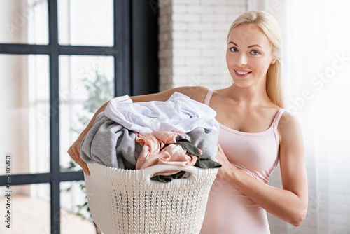 Fotografie, Obraz Smiling caucasian woman carrying laundry basket at home