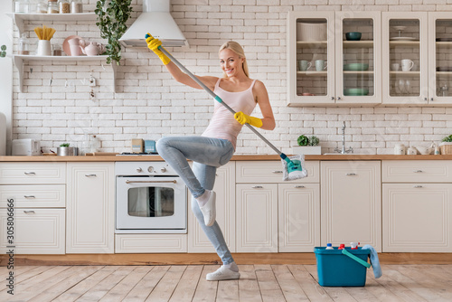 Obraz Happy woman dancing with mop and having fun while cleaning home - fototapety do salonu