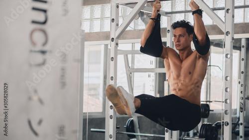 Fotografie, Tablou caucasian strong man doing exercise on horizontal bar in gym club
