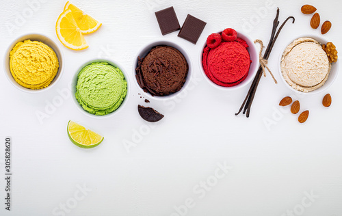 Fotografie, Obraz  Various of ice cream flavor ball blueberry ,lime ,pistachio ,almond ,orange ,chocolate and vanilla set up on white wooden background