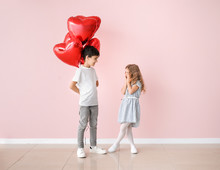 Little Boy Giving Air Balloons To Cute Girl On Color Background. Valentines Day Celebration