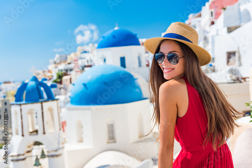 Fototapeta Europe Greece Santorini travel vacation woman on famous santorini Oia island travel destination. Happy young tourist girl in hat and sunglasses relaxing at blue dome church. Summer wanderlust. obraz