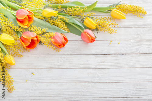 Foto tulips and mimosa on white wooden background
