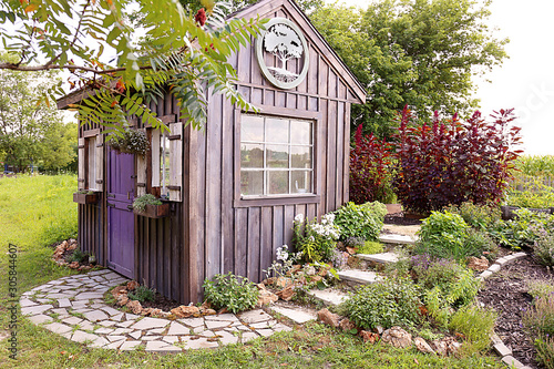 Foto Custom Built Cottage Like Garden Shed with Cobblestone Sidewalk and Wood Board a