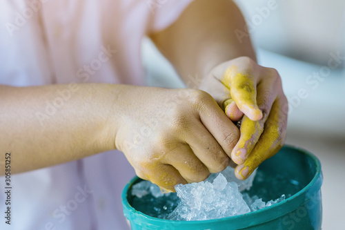 Close up to wash hands stained with yellow oil color by ice in a green bowl Wallpaper Mural