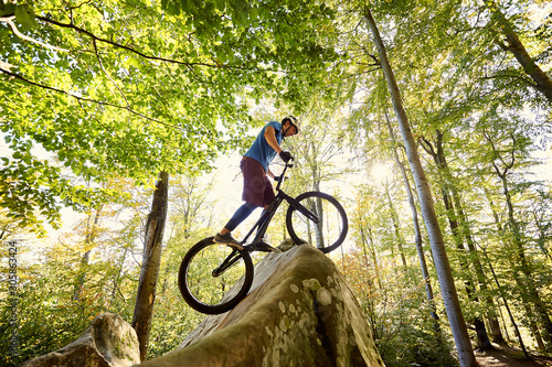Leinwand Poster Male professional cyclist balancing on trial bicycle, making acrobatic trick on big boulder in the forest outdoor on summer sunny day