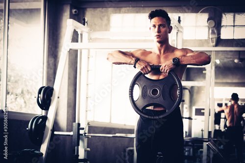 Young strong muscular man with big muscles focused on weight training with dumbbell hard core workout in the gym Billede på lærred