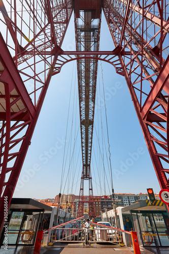 Bizkaia red iron hanging bridge and Nervion river. Euskadi