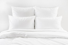 White Bed Isolated, Four White Pillows And Duvet On A Bed
