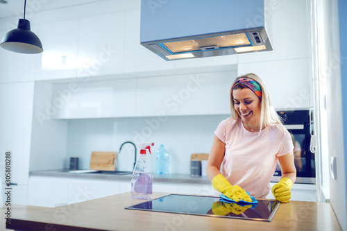 Cuadros en Lienzo Worthy cheerful caucasian blond housewife with rubber gloves on hands cleaning stove