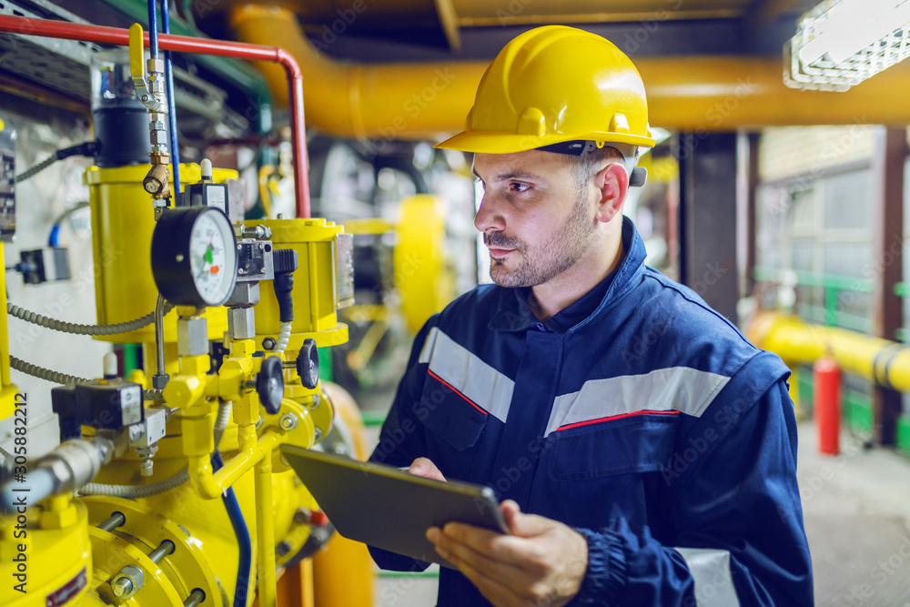 Fototapeta Serious caucasian unshaven worker in protective uniform and with hardhat using tablet for checking temperature in pipes. Factory interior.