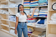 Cheerful African American Woman Stand Near Shelves With Towels In The Self-service Laundry.