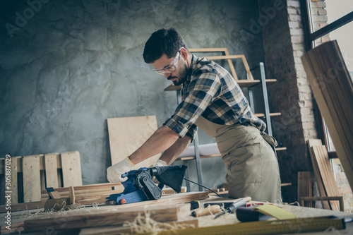 Side profile photo of serious pensive confident man processing wood with sander Wallpaper Mural