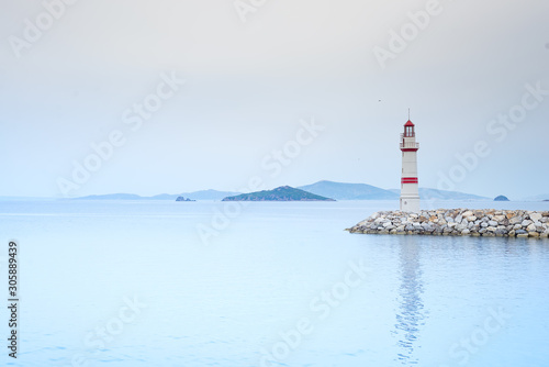 Lonely lighthouse on a stone road in the middle of the sea with views of the mou Canvas Print