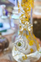 Vertical Closeup Shot Of A Cannabis Bong With Golden Patterns On Blurred Background
