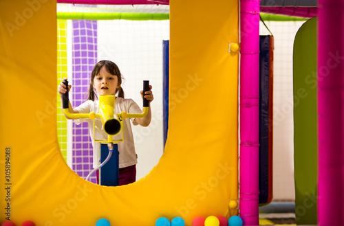girl preschooler shoots from a yellow game blaster with foam soft balls Wallpaper Mural