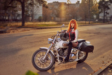 Motorcycle Cruiser And Woman Biker On The Road In The Autumn City At Sunset