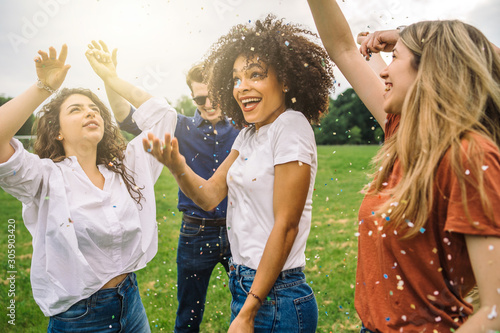 Group of friends at the park dancing under a rain of confetti - Millennials have fun in a public garden in summer at sunset - 305903420