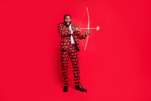Full Body Photo Of Funny Dark Skin Man With Bow And Love Arrow Amour Cupid Role See Good Couple Wear Hearts Pattern Suit Shirt Necktie Tie Boots Outfit Isolated Red Color Background