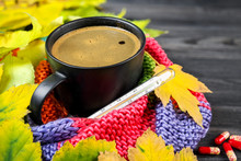 Autumn Still Life: A Cup Of Hot Coffee And A Thermometer Wrapped In A Warm Scarf, Yellow Leaves.