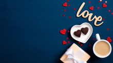 """Valentine Day Banner. Flat Lay Gift Box, Coffee Cup, Heart Shaped Candy, Wooden Text Sign """"Love"""" On Blue Background. Love And Romance Concept."""