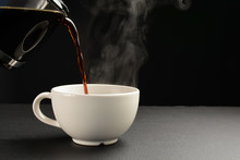 Pour The Hot Black Coffee Into A White Cup On The Black Table.