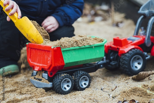 Child playing with sand and plastic toy trucks in a sand box in a park Wallpaper Mural