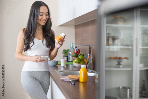Fotografia Woman with a dietary supplement in the kitchen