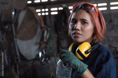 Tired Asian female workshop engineer holding water bottle wearing industrial saf Wallpaper Mural