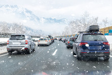 Winter Highway With Many Different Cars Stucked In Traffic Jam Due Ti Bad Weather Conditions. Vehicles On Road During Heavy Snowstorm And Blizzard On Cold Winter Day In Austria Near Germany Border